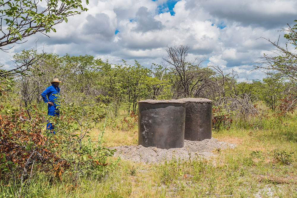 Mbati standing in front of some of his charcoal kilns ready for burning