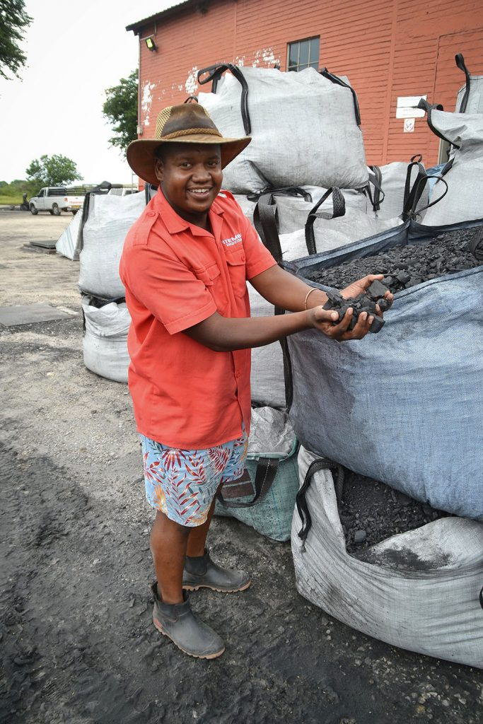 Matti Intamba proudly shows off their charcoal production